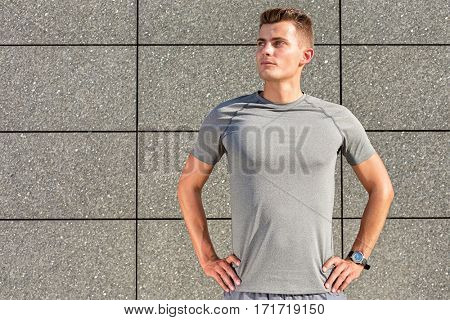 Determined jogger standing against tiled wall outdoors