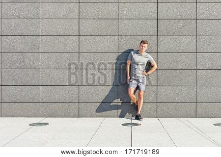 Full length portrait of confident sporty man leaning on tiled wall
