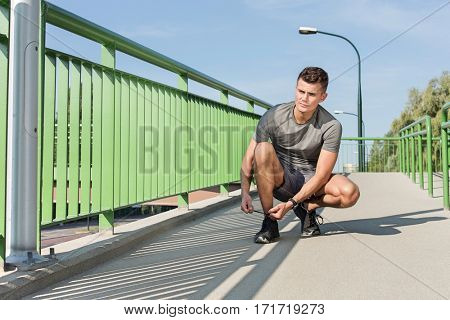 Full length of sporty man tying shoelace on bridge