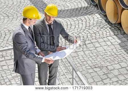 High angle view of young male architects examining blueprint by railings