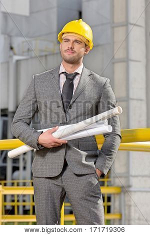 Young male architect with rolled up blueprints at construction site