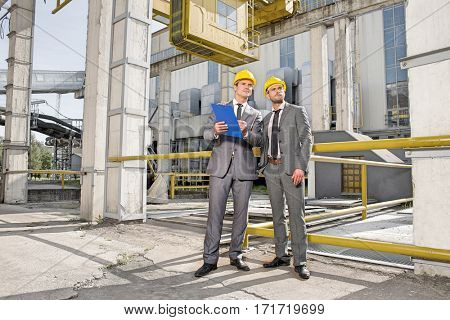 Full length of young male engineer with clipboard looking away at construction site