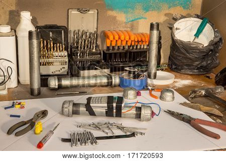 Pipe bomb makers workshop with tools and nails