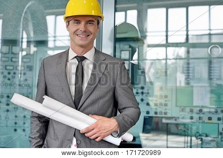 Portrait of smiling young architect holding rolled up blueprints in industry