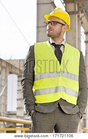 Young male architect in protective workwear standing hands in pockets at construction site