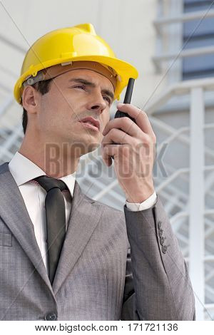 Young male architect talking on walkie-talkie against building