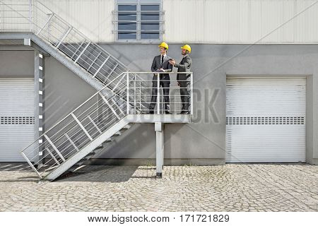 Young male architects with clipboard discussing on stairway