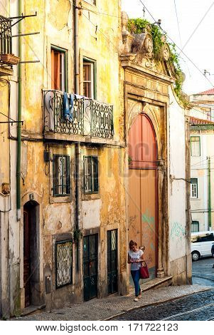Lisbon, Portugal - Septmember 19, 2016: Street scene in old neighbourhood Mouraria, single young woman walking up on the sidewalk