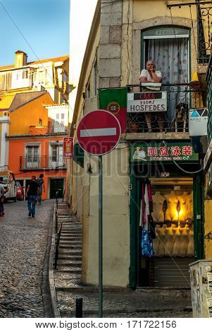 Lisbon, Portugal - Septmember 19, 2016: Street scene in old neighbourhood Mouraria, older woman standing on her balcony looking around, in the distance a few men walk up the hill