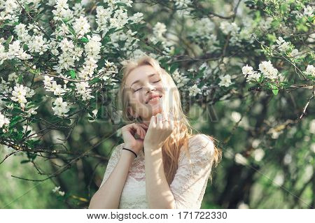 Young gentle blonde woman in blooming garden. Girl enjoying the fragrance of spring. She clothed white lacy dress.
