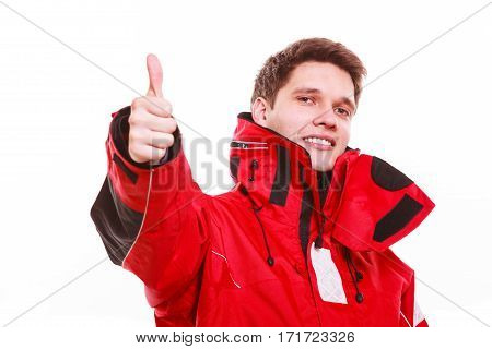 Man wearing protective clothing. Young male in red oilskin. Adventure danger waterproof action outdoor concept.