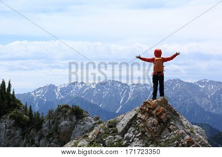 successful woman hiker enjoy the view on mountain top rock