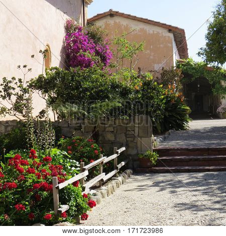 This is an image of an outer courtyard of the Carmel Mission taken on a bright sunny day.