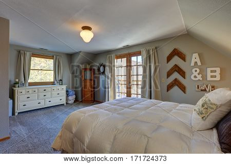 Tranquil Bedroom With Sloped Ceiling And Doors To Nice Deck.