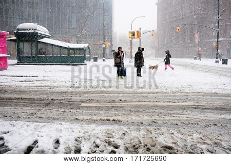 NEW YORK - FEB 9: Pedestrians stand near Astor Place as snow falls on February 9, 2017 in New York. Snowfall totals of approximately six inches fell in and around NYC.