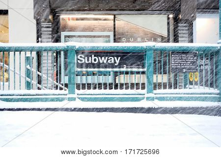 NEW YORK - FEB 9: View of a subway station entrance as snow falls on February 9, 2017 in New York. Snowfall totals of approximately six inches fell in and around NYC.
