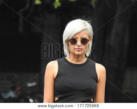 A Serious Platinum Blonde Female Wearing Sunglasses