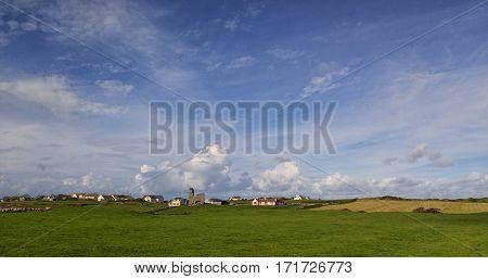 Doolin village landscape in County Clare, Ireland. Medieval Doonmacfelim castle ruins stand amid modern homes.