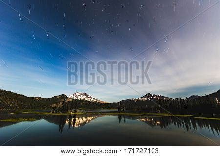 Beautiful lake mountains and sky with clouds over Sparks Lake near Bend Oregon. Sunset with clouds in blue and orange sky. Water reflecting clouds and light.