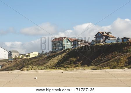 Modern houses sit on a ridge on a beach in Oregon. Partly cloudy summer day at Nye Beach Newport Oregon.