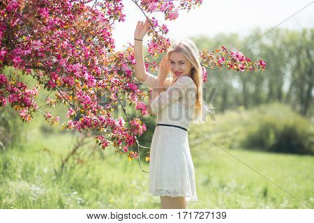 Beautiful young girl lovely smilling and enjoying warm day in park during cherry blossom season on a nice spring