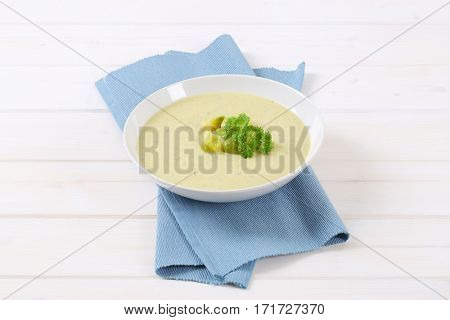 plate of vegetable soup with Brussels sprouts on blue place mat