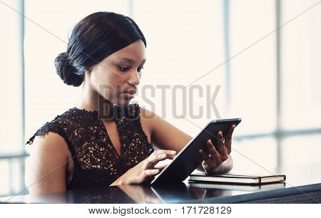 Black female using a digital tablet while seated at a counter with a serious facial expression as she concentrates on completing her current task.