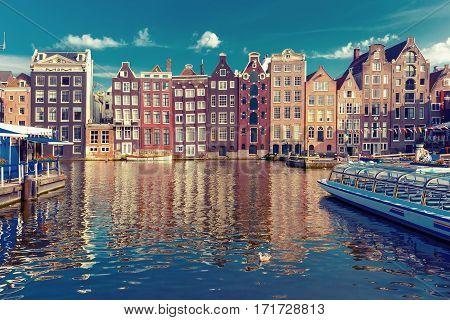 Beautiful typical Dutch dancing houses at the Amsterdam canal Damrak in the sunny evening, Holland, Netherlands.