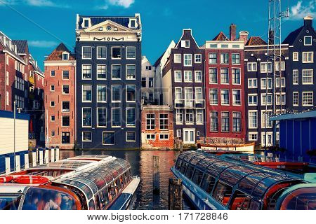 Beautiful typical Dutch dancing houses and tourist boats at the Amsterdam canal Damrak in sunny day, Holland, Netherlands.