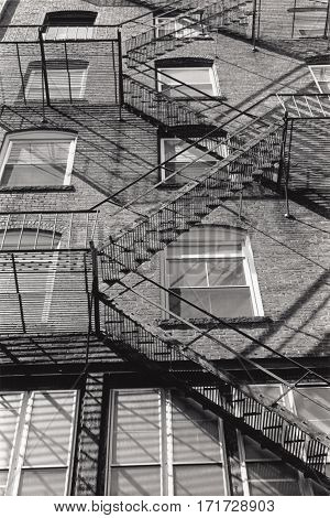 Artistic black and white photo of a fire escape climbing a building