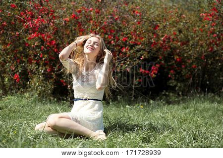 Young blonde woman in lacy white dress enjoying aroma blooming garden in the air. Girl sitting on fresh grass.