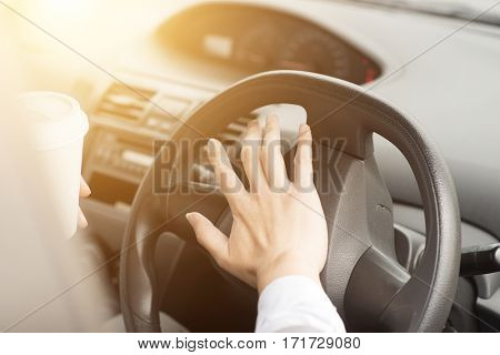 Concept photo of close up hand on steering honking while driving in morning.