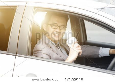 Asian business man driving a car and holding paper cup of coffee in morning with beautiful sunlight.