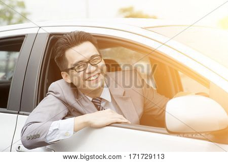 Happy Asian driver sitting in his car and smiling.