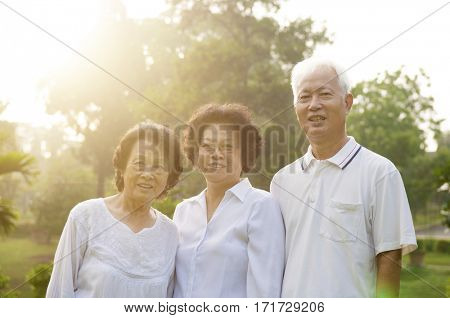 Group of healthy Asian seniors having good time at outdoor nature park, in morning beautiful sunlight at background.