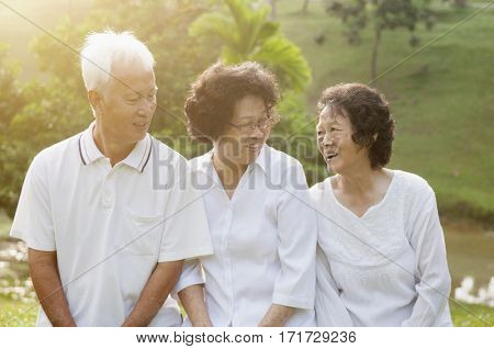 Group of healthy Asian seniors chatting at outdoor nature park, in morning beautiful sunlight at background.
