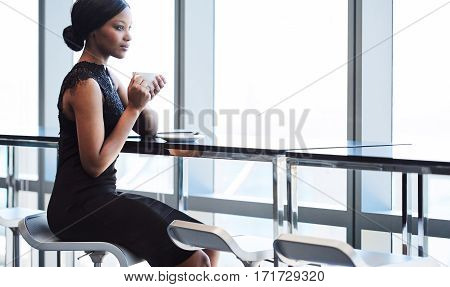 Wide horizontal image of a classy African American woman wearing an attractive black dress while seated on a bar stool at a counter next to large glass pane windows.