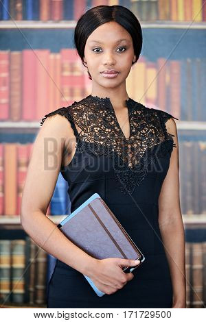 Portrait image of well dressed black woman wearing a smart black dress while standing in front of a book shelf holding a notebook and digital tablet under her arm in her hands.