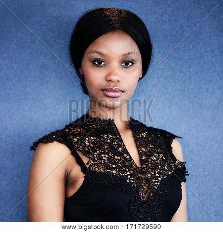 Close up square image of attractive african woman wearing a black dress while looking straight into camera with a blue background.
