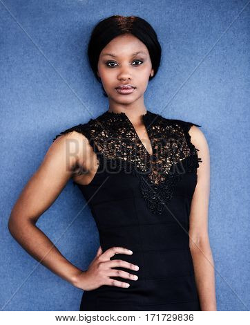 African American woman standing in front of blue background with one hand on her hip, while looking straight into the camera, showing off her new black dress.