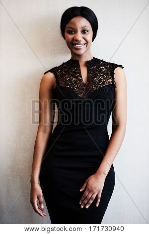 Well dressed attractive young black woman wearing a slim black dress smiling at the camera wile posing in front of a textured beige wall.