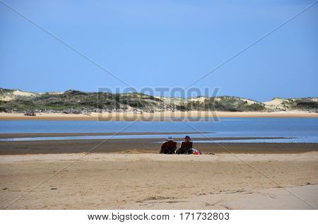 Old couple resting on the beach. View of coastline of Marlo Recreational Reserve in summer Marlo in Victoria Australia. The Snowy River flows into the Bass Strait near Marlo.