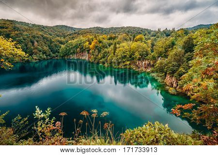 Emerald blue Plitvice lake in Croatia surrounded with autumn colors.