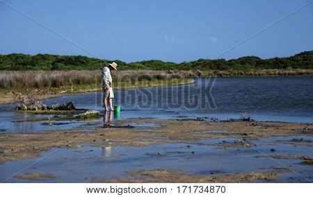 Mallacoota, Australia - Jan 5, 2017. Man collecting baits. Man standing in the water at the beach.