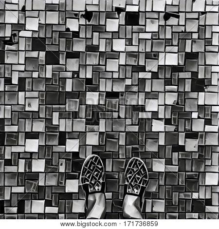 Female feet in ethnic shoes on colorful bricks. Digital illustration with black relief. Walking in urban area. Comfortable shoes for travel. Modern asian city. Going around by the mosaic path.