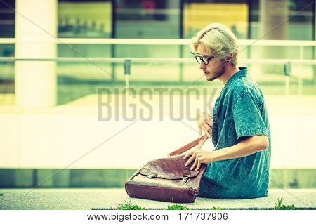 Male fashion student concept. Guy with vintage bag wearing jeans outfit and eccentric sunglasses sitting on white ledge next to modern building
