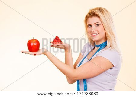 Diet sweets temptation healthy choices concept. Woman with measuring tape around her neck choosing between apple and sweet cupcake making decision.