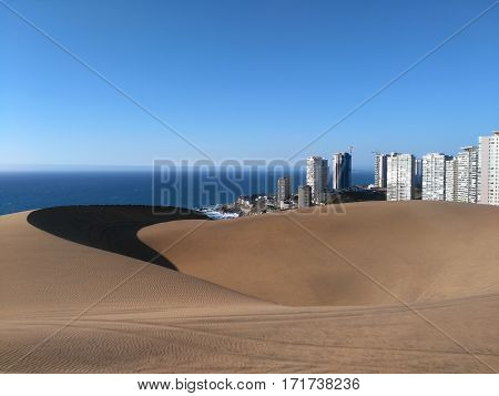 Sand dunes and cityscape behind them under blue sky