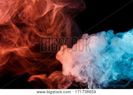 Abstract smoke Weipa. Personal vaporizers fragrant steam. The concept of alternative non-nicotine smoking. Turquoise orange smoke on a black background. E-cigarette. Evaporator. Taking Close-up. Vaping.