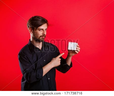 Man holding an empty cube. Advertising Space. Attractive man shows space for copy. Forefinger. Tricky glance